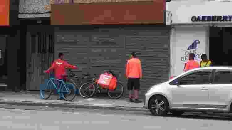 Na Tijuca, entregadores conversam em calçada aguardando novos pedidos - Igor Mello/ UOL - Igor Mello/ UOL