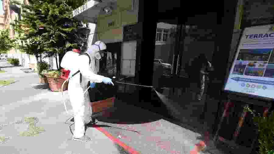Um limpador usando um equipamento de proteção higieniza a entrada do Hotel Atlante Star Roma, perto do Vaticano, enquanto a Itália se prepara para um alívio gradual das restrições de bloqueio que foram impostas para combater a propagação do coronavírus - Alberto Lingria/Reuters