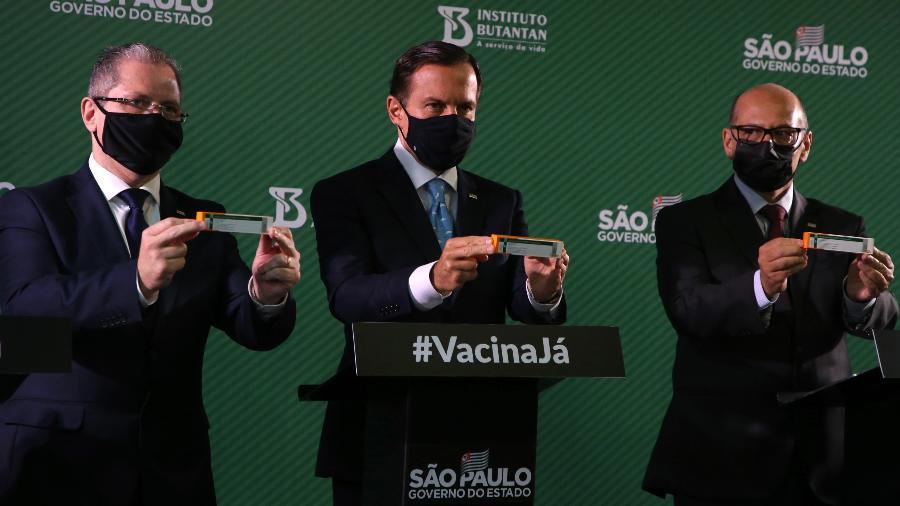 O governador de São Paulo, João Doria (PSDB), segura caixa da CoronaVac ao lado do secretário estadual de Saúde, Jean Gorinchteyn, e o diretor do Instituto Butantan, Dimas Covas - Divulgação