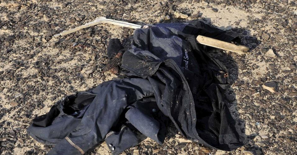 31.out.2015 - Roupas são encontrados no chão em vistoria ao local onde estão espalhados os destroços do avião russo que caiu nesta manhã, no Egito. O acidente provocou 224 mortes. A aeronave, um Airbus-321 da companhia Kogalimavia (conhecida como Metrojet), despencou na península do Sinai minutos após a decolagem, com 217 passageiros e sete tripulantes a bordo. A maioria dos passageiros era formada por turistas russos