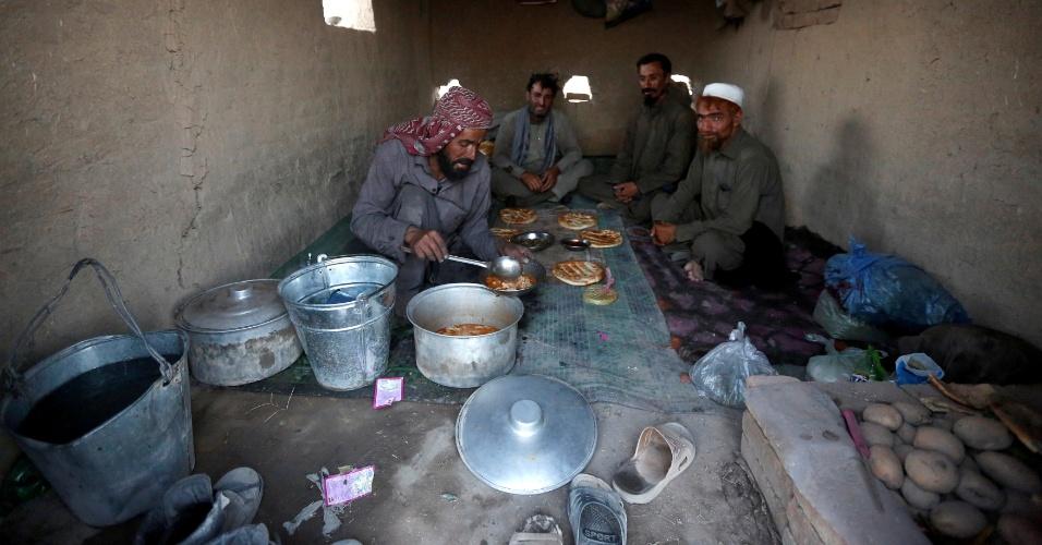 4.jul.2016 - Shir Alam (à esq.), 31, prepara shorba, uma sopa afegã feita de carne ou cordeiro, que é servida com pão e batatas, antes da quebra de jejum diária do mês sagrado do Ramadã, em Cabul, no Afeganistão