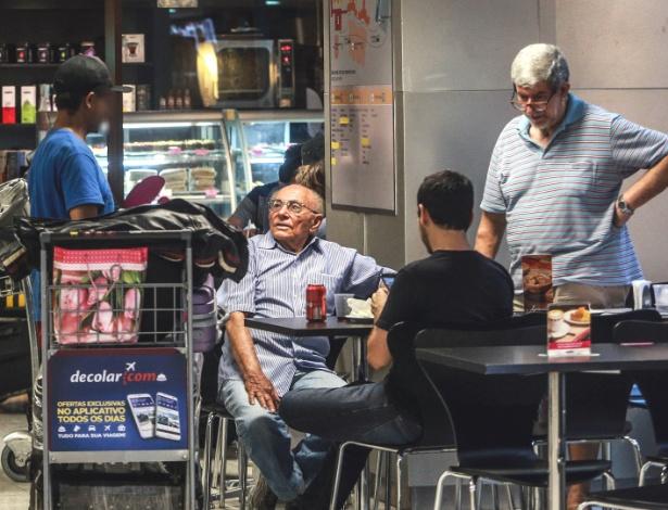 Com mochila nas costas, pedinte (à esq.) aborda família em lanchonete em Cumbica
