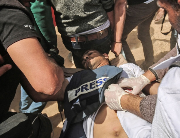 Pessoas prestam assistência a videojornalista e fotógrafo palestino baleado