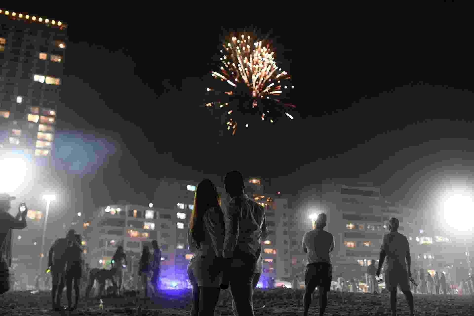 Pessoas admiram a queima de fogos em Copacabana, no Rio - Lucas Landau / Reuters