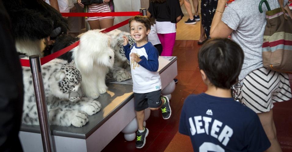 15.jul.2015 - Garoto pula ao ver um panda gigante de pelúcia na tradicional loja de brinquedos FAO Schwarz, que fica na Quinta avenida, em Nova York (EUA), nesta quarta-feira (15), no seu último dia de funcionamento. A FAO Schwarz já teve vários endereços na