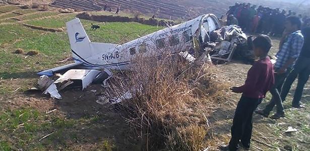 Nepaleses observam destroços de aeronave que caiu no distrito de Kalikot, no Nepal