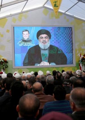 6.mar.2016 - Partidários do Hezbollah ouvem pronunciamento do líder do movimento xiita libanês, Hassan Nasrallah