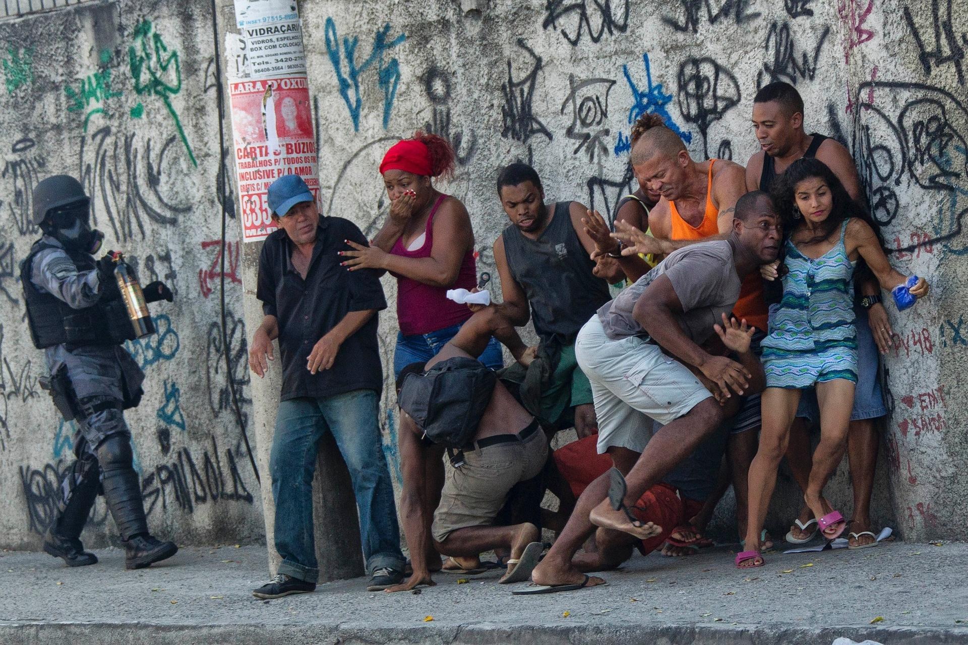28.mar.2016 - Manifestantes correm de policial em Madureira, zona norte do Rio de Janeiro. Ao menos cem moradores do Morro do Cajueiro protestam pela morte de Ryan Gabriel, de 4 anos. O menino foi atingido por uma bala no peito em um tiroteio entre traficantes de facções rivais no domingo (27). Durante o protesto, os moradores também fecharam os dois sentidos da avenida Ministro Edgard Romero, e incendiaram dois ônibus e uma estação dos ônibus do BRT