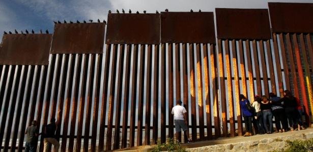 Em Tijuana (México), pessoas falam com parentes que estão do outro lado da cerca que separa o México dos Estados Unidos