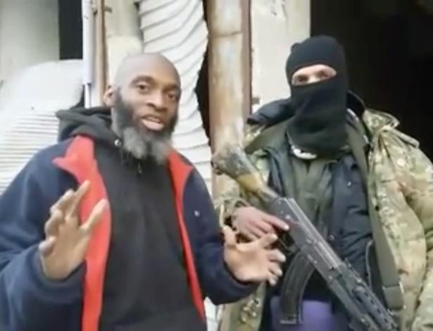 Bilal Abdul Kareem ao lado de um combatente mascarado e com cinturão explosivo na Síria