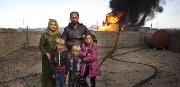 Ali Hassan, sua mulher Fatima Mahmoud e suas três crianças vivem perto de um poço de petróleo em chamas