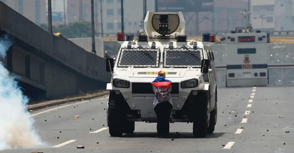 """19.abr.2017 - Segurando com uma bandeira venezuelana, Maria Jose Castro, 54, bloqueia a passagem de veículo blindado em Caracas. O fotógrafo Juan Barreto diz que ficou impressionado """"com sua força de vontade em ficar ali"""". A polícia anti-distúrbios jogou duas bombas de gás lacrimogêneo para fazê-la sair, mas ela continuou firme e forte, pressionando um lenço contra o rosto, até que a polícia veio de moto e a retirou. """"Me doeu ver como eles estavam disparando contra crianças"""", disse ela mais tarde, em referência às balas de borracha usadas pela polícia contra os manifestantes"""
