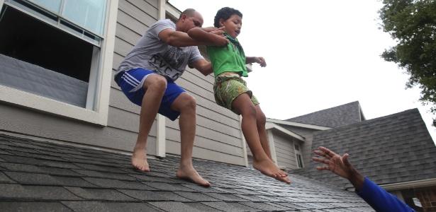 Criança é resgatada pelo telhado e levada para um dos barcos que atuam no resgate dos sobreviventes nas áreas alagadas pela passagem da tempestade Harvey - Barbara Davidson/The New York Times