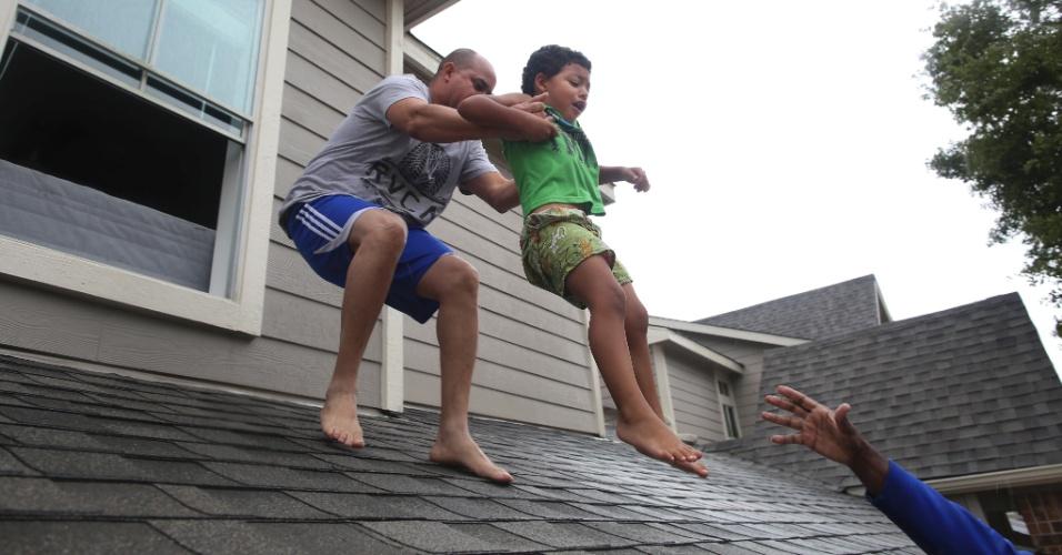 29.ago.2017 - Criança é resgatada pelo telhado e levada para um dos barcos que atuam no resgate dos sobreviventes nas áreas alagadas pela passagem da tempestade Harvey