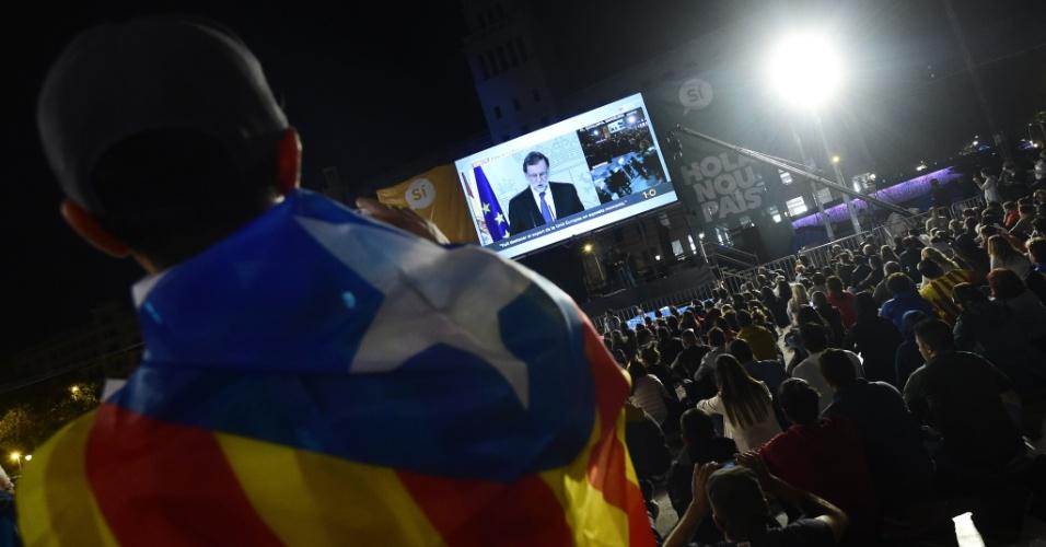 1º.out.2017 - Pessoas assistem declaração do primeiro-ministro espanhol, Mariano Rajoy, após o encerramento da votação do referendo