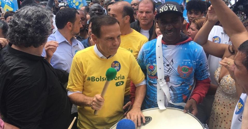"""27.out.2018 - João Doria (PSDB) toca surdo ao som de """"É campeão"""", no Capão Redondo, zona sul de São Paulo"""