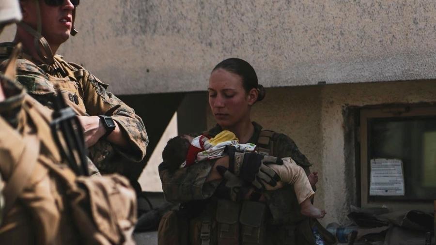A sargento Nicole Gee (em pé) foi uma entre os 13 militares americanos mortos nas explosões próximas ao aeroporto de Cabul. Dias antes de morrer ela publicou em suas redes sociais uma foto segurando um bebê afegão no colo - Reprodução/Instagram
