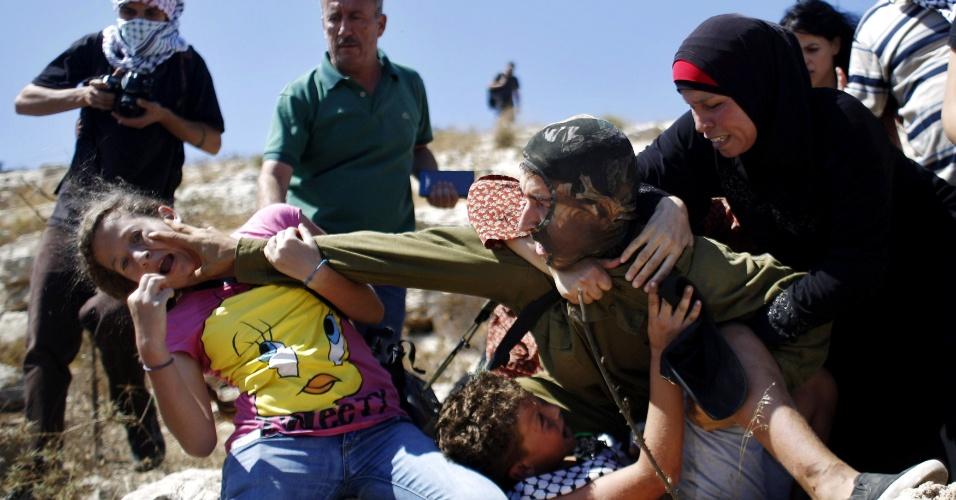 Soldado israelense armado derruba um menino de braço quebrado contra as pedras antes de ser agredido pelos parentes da criança na Cisjordânia no dia 28 de agosto