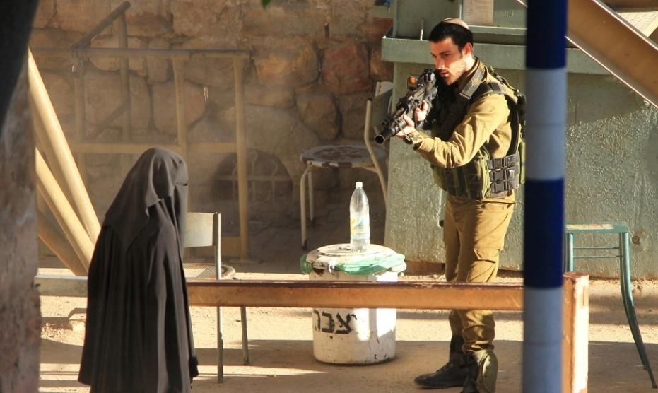 22.set.2015 - Soldado israelense aponta arma para a estudante palestina Hadeel al-Hashlamon, 18, morta a tiros minutos depois pelo mesmo milita. A versão do Exército é que ela ameaçou-o com uma faca. Testemunhas dizem que ela não queria ser revistada por homens