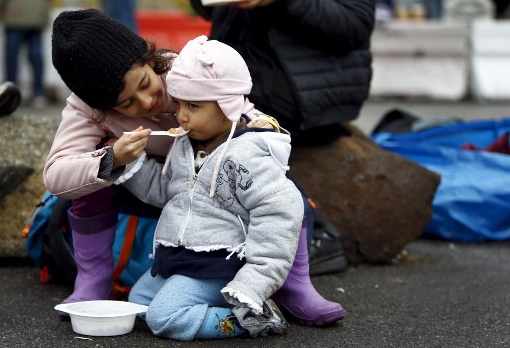 29.out.2015 - Menina de oito anos dá sopa para seu irmão, de um ano, enquanto o grupo de refugiados do qual fazem parte aguarda para atravessar a fronteira da Áustria com a Alemanha, em Achleiten, na Áustria