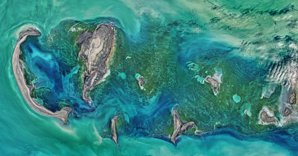 25.abr.2016 - RISCOS MISTERIOSOS - Um satélite da Nasa (Agência Espacial Norte-Americana) registrou as cores naturais do mar Cáspio, ao redor do arquipélago Tyuleniy. Além da impressionante cor do mar, os cientistas também ficaram impressionados com as linhas brancas que aparecem entre a vegetação verde escura, queriam entender como as tais linhas se formaram. Após análise, pesquisadores notaram que parte dos riscos podiam ter origem humana, criados por objetos que se arrastaram no local. Porém, a literatura científica sugeriu que a maior parte das marcas apareceu devido ao gelo. Em janeiro, blocos de gelo estavam na região, mas foram derretendo e se locomoviam com a força dos ventos e correntes, marcando o solo