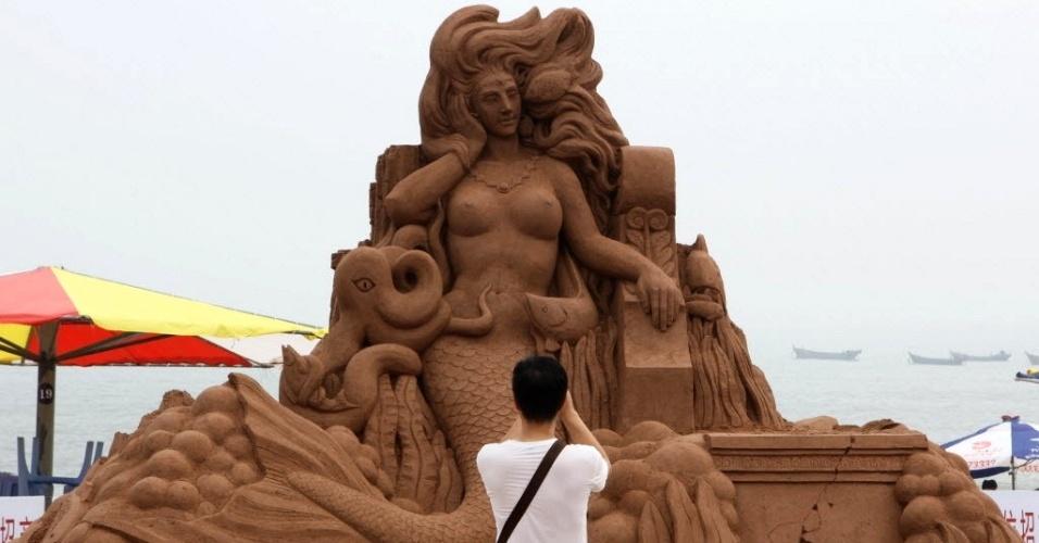 23.jul.2016 - Homem tira foto de escultura de areia durante Festival Internacional de Cultura de Praia de Dalian, na província de Liaoning (China), neste sábado (23)