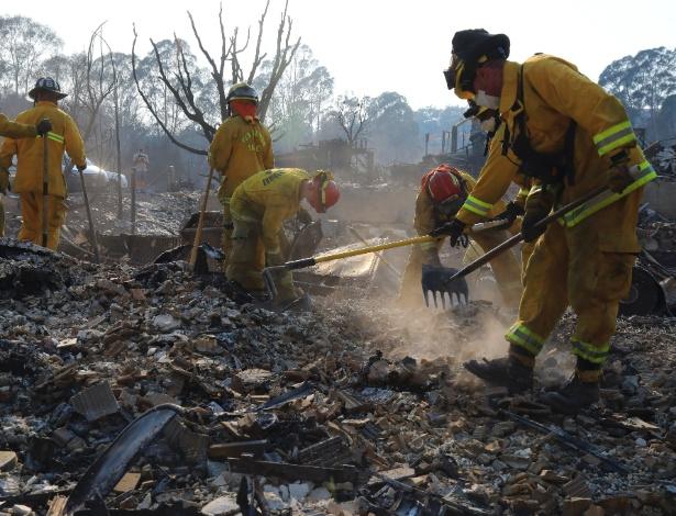 Bombeiros mexem em resíduos de uma casa após incêndio atingir o bairro em Santa Rosa, Califórnia