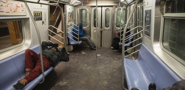 Pessoas dormem em vagão da linha E do metrô de Nova York durante onda de frio