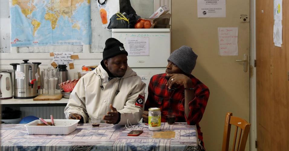 Imigrantes conversam em um abrigo da organização Tous Migrants