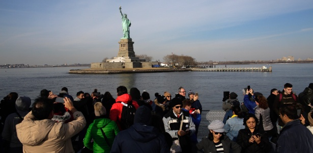 21.jan.2018 - Turistas tiram fotos da Estátua da Liberdade, que estava fechada à visitação por causa do shutdown; ela foi reaberta nesta segunda (22)