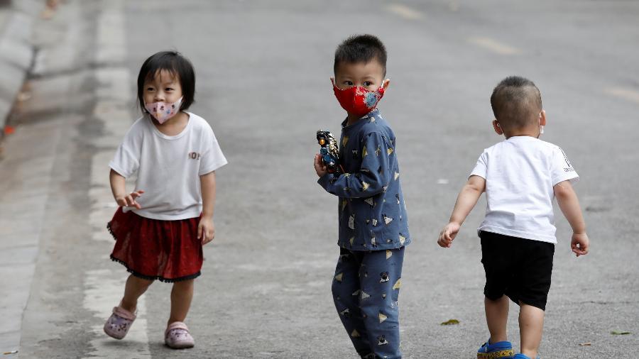 Crianças usam máscara de proteção enquanto brincam em Hanoi, no Vietnã. Elas moram na casa de uma pessoa diagnosticada com o novo coronavírus - Reuters