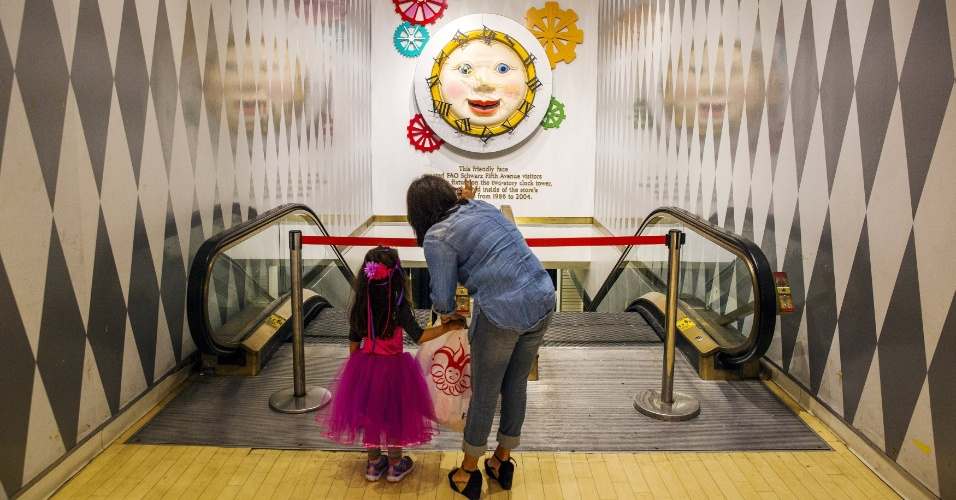 15.jul.2015 - Mulher e sua filha observam um relógio que já esteve pendurado na entrada principal da tradicional loja de brinquedos FAO Schwarz, que fica na Quinta avenida, em Nova York (EUA), nesta quarta-feira (15), no seu último dia de funcionamento. A FAO Schwarz já teve vários endereços na