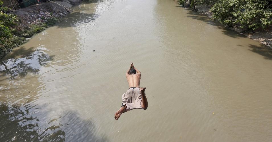 25.abr.2016 - Por causa do forte calor, homem salta em rio para se refrescar em Calcutá, na Índia