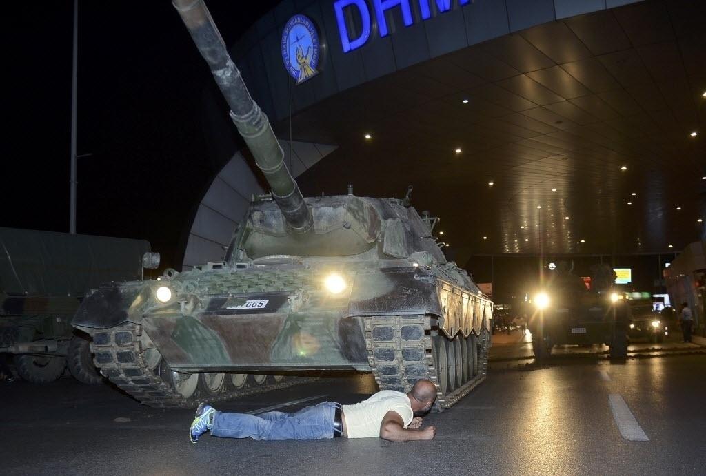 15.jul.2016 - Homem deita em frente de um tanque do Exército turco no aeroporto de Ataturk, em Istambul, na Turquia. O primeiro-ministro da Turquia, Binali Yildirim, afirmou em rede nacional que o país passa neste momento por uma tentativa de golpe militar. Segundo relatos de testemunhas, as pontes sobre o Estreito de Bósforo, em Istambul, foram fechadas