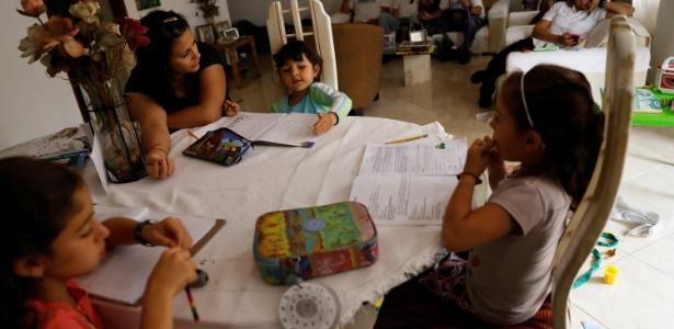 21.jun.2017 - Crianças não vão ao colégio e fazem tarefa em casa com sua mãe, em dia de protestos na Venezuela