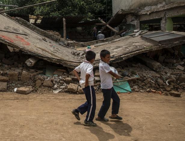 Crianças passam em frente a construção totalmente destruída pelo terremoto em San Francisco Xochiteopan, no México