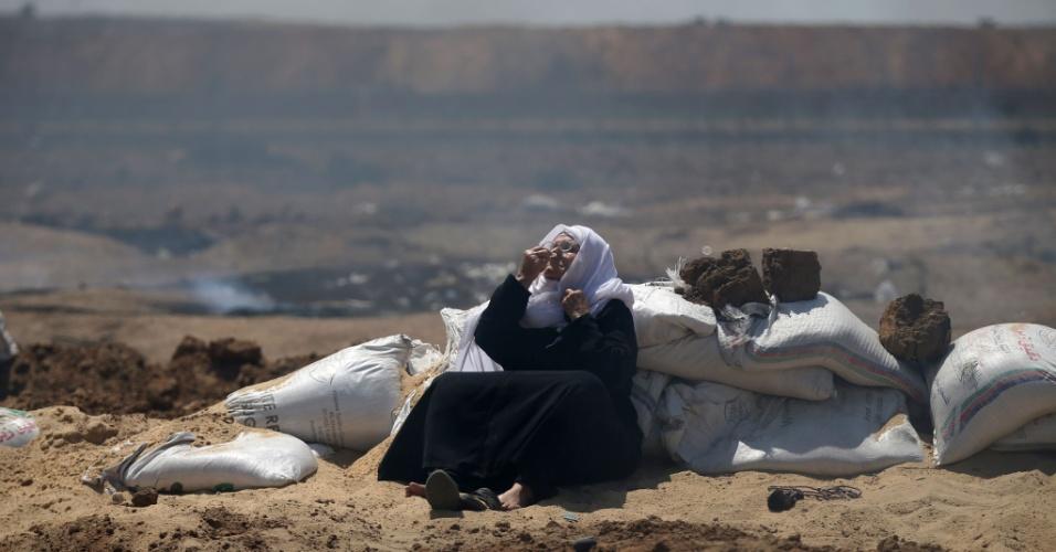 14.mai.2018 - Mulher inala substância para reduzir efeitos de gás lacrimogêneo durante manifestação palestina na Faixa de Gaza