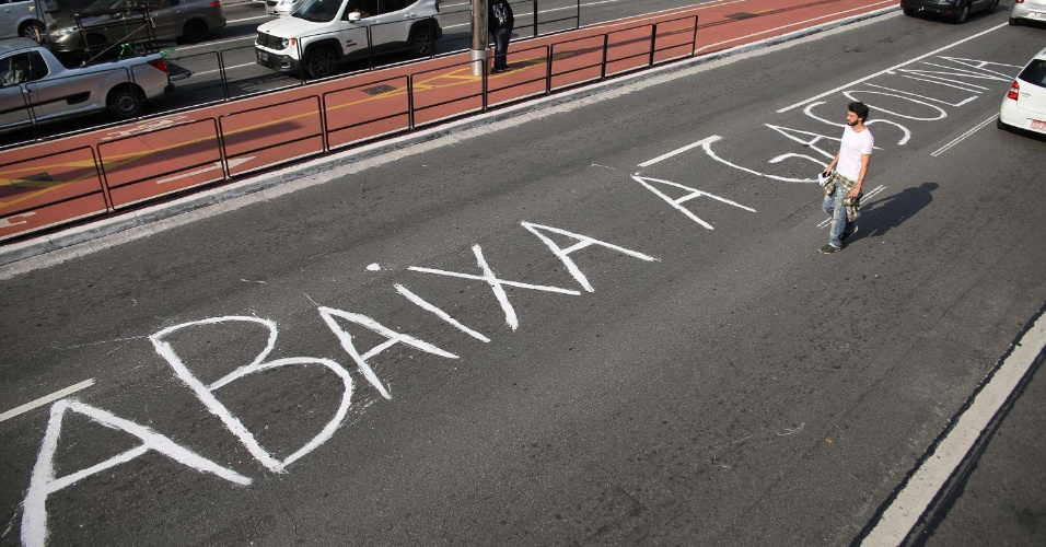 """21.mai.2018 - Manifestante faz pichação no asfalto da Avenida Paulista com a mensagem """"Abaixa a gasolina"""", em protesto contra os aumentos nos preços dos combustíveis em São Paulo, nesta quinta-feira"""