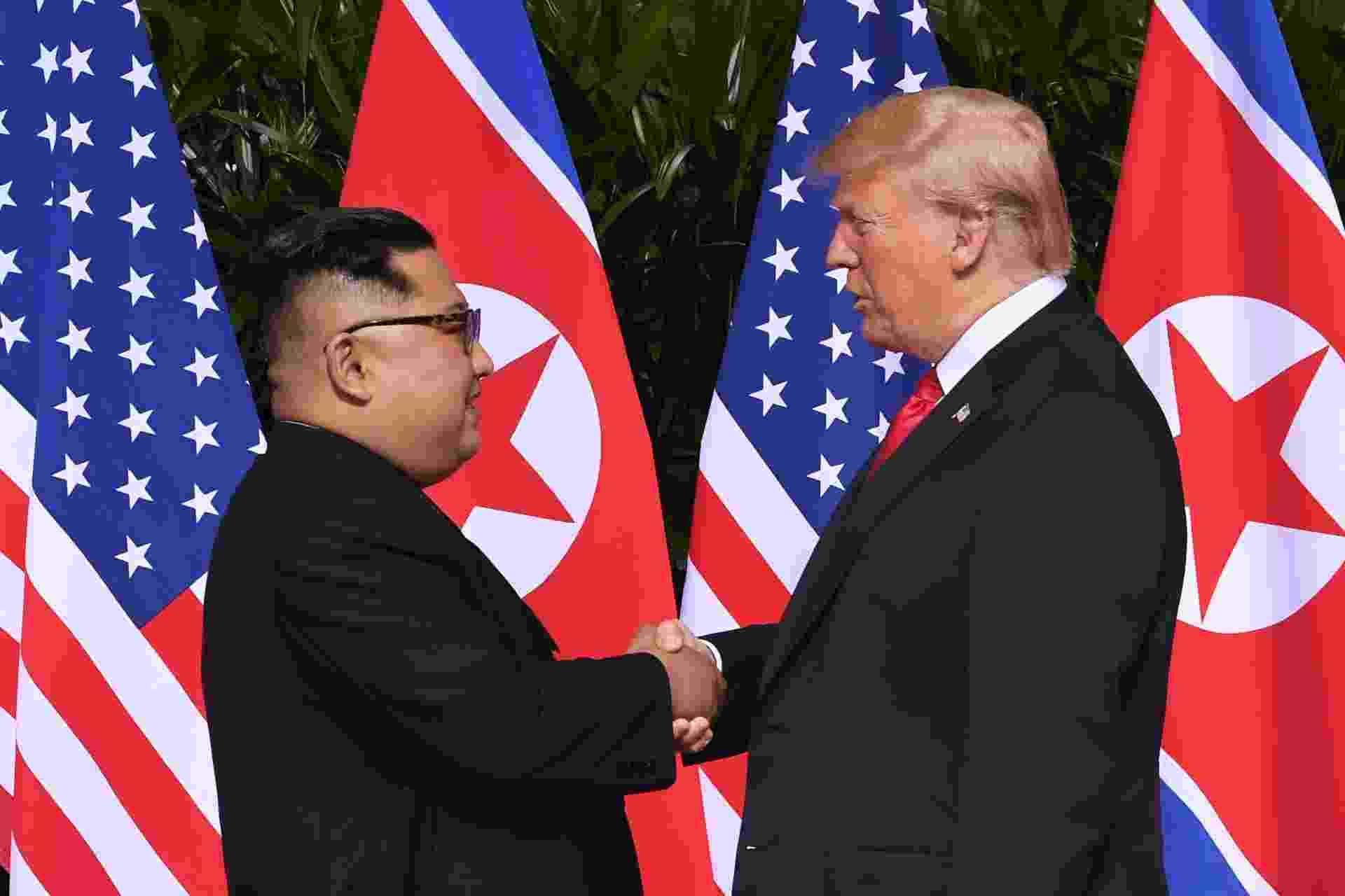 11.jun.2018 - Donald Trump e Kim Jong-un se cumprimentam com um aperto de mão em encontro histórico após décadas de tensões provocadas pelas ambições nucleares de Pyongyang - Saul Loeb/AFP