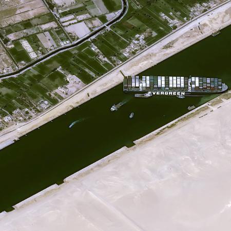 O Ever Given, que tem 400 metros de comprimento (quase quatro campos de futebol), ficou atravessado diagonalmente dentro do Canal de Suez, que não tem mais de 200 metros de largura, bloqueando o tráfego nos dois sentidos - Reuters