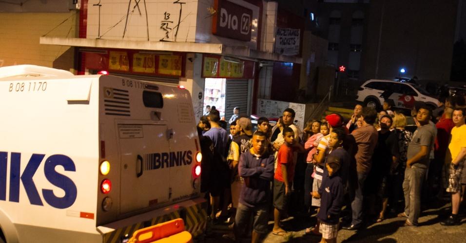 8.dez.2015 - População observa local onde houve tentativa de assalto a carro-forte, que terminou com a morte de um vigilante e de um suspeito no fim da tarde de terça-feira, na avenida do Oratório, zona leste de São Paulo