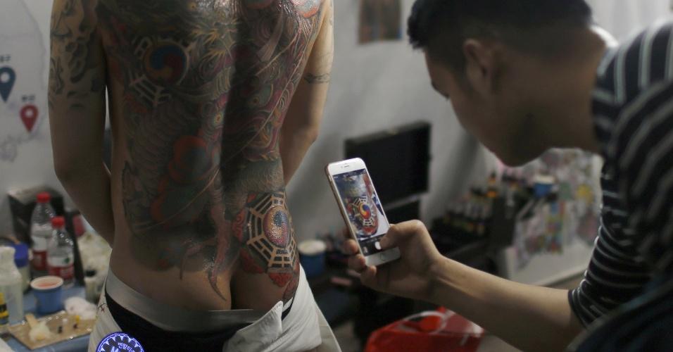 23.abr.2016 - Homem faz fotos das tatuagens nas costas de um participante de um concurso após exibição no Festival Internacional de Artes de Tatuagens em Xangai, na China