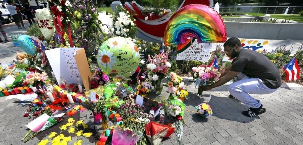 14.jun.2016 - Homem coloca flores em um memorial improvisado para as vítimas do massacre na boate gay em Orlando, nos Estados Unidos. O local das homenagens fica a poucos quarteirões da casa noturna onde houve o tiroteio