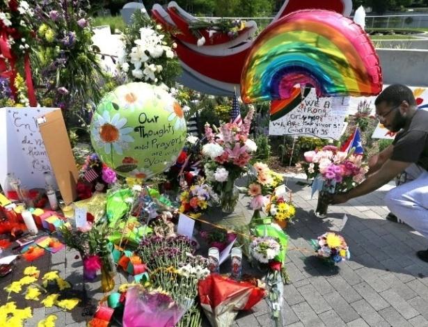 Homem coloca flores em um memorial improvisado para as vítimas do massacre na boate gay em Orlando, nos Estados Unidos - Joe Burbank/ Orlando Sentinel