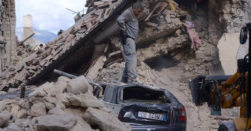 24.ago.2016 - Homem fica em pé em cima de carro danificado após o terremoto que atingiu Amatrice, na Itália. O incidente deixou dezenas de mortos e feridos