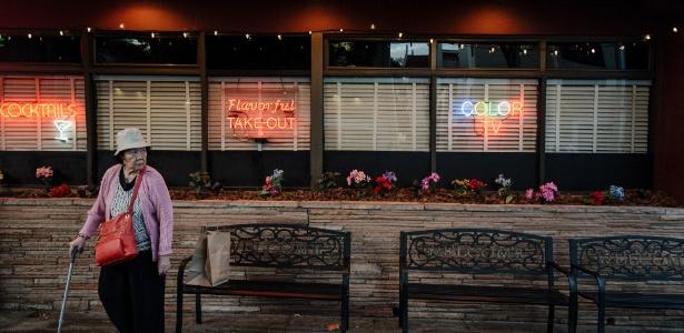 Mulher passa diante do restaurante Buca di Beppo, em Palo Alto