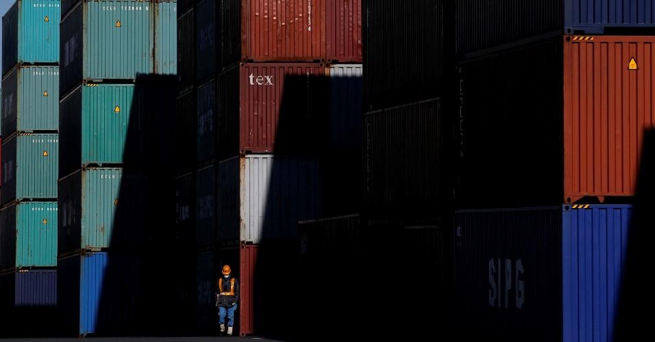 21.set.2016 - Trabalhador anda em uma área de containeres em no porto de Tóquio, no Japão