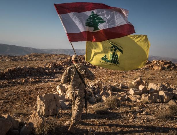 Combatente do Hizbollah carrega a bandeira do Hizbollah (amarela) e a bandeira do Líbano em Jaroud Arsal, uma área libanesa próxima à fronteira com a Síria - SERGEY PONOMAREV/NYT