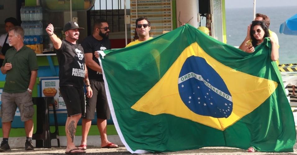 Confiantes, apoiadores de Jair Bolsonaro agitam bandeira do Brasil na Barra da Tijuca, zona oeste do Rio de Janeiro
