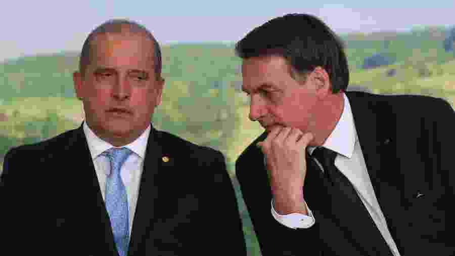 18.jun.2019 - O ministro da Casa Civil Onyx Lorenzoni conversa com o presidente Jair Bolsonaro durante cerimônia no Palácio do Planalto - Andre Coelho/Folhapress